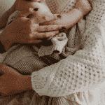 Mutter hält Baby im Arm zeigt wie eine Schwangerschaftsmassage die Bindung fördern kann